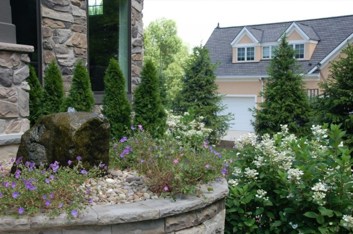 Raised Sandstone Wall with Barnstone Water Feature Surrounded by Perennials